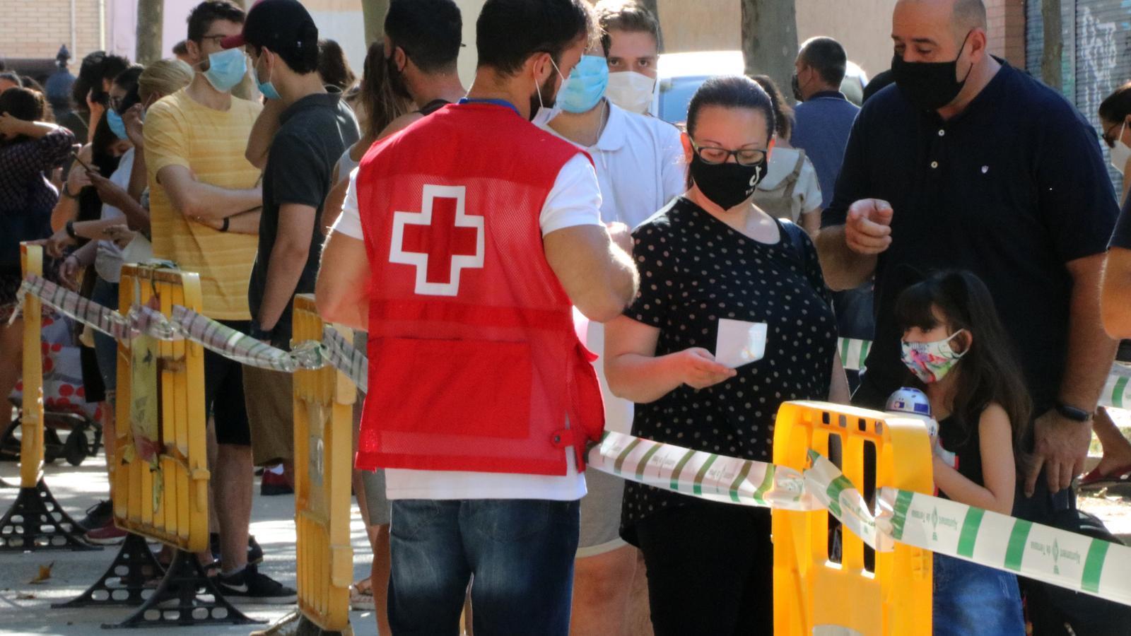 Veïns de Terrassa esperant per fer-se la prova PCR mentre un voluntari de la Creu Roja els informa del procediment. Imatge del 7 d'agost del 2020