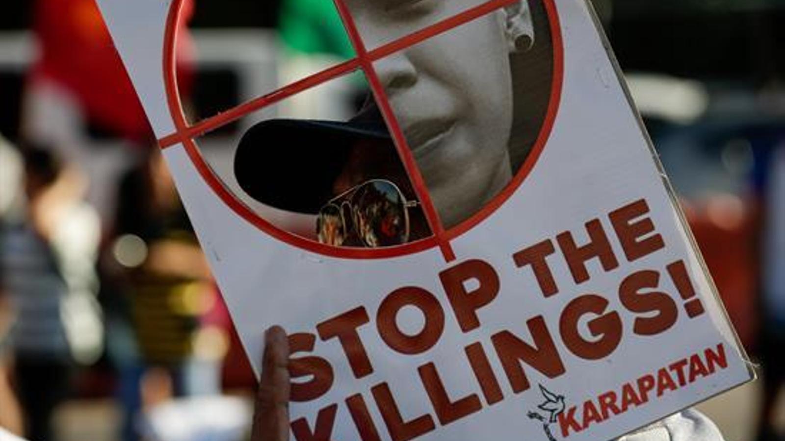 Un cartell demanant acabar amb els assassinats en nom de la seguretat, en la manifestació de Manila.