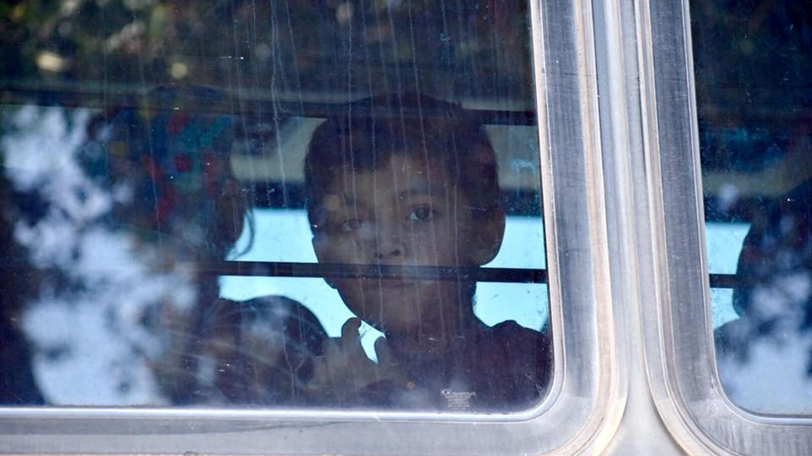 Un nen mirant per la finestra en l'autobús en què serà traslladat a un centre de detenció per a migrants, a Texas