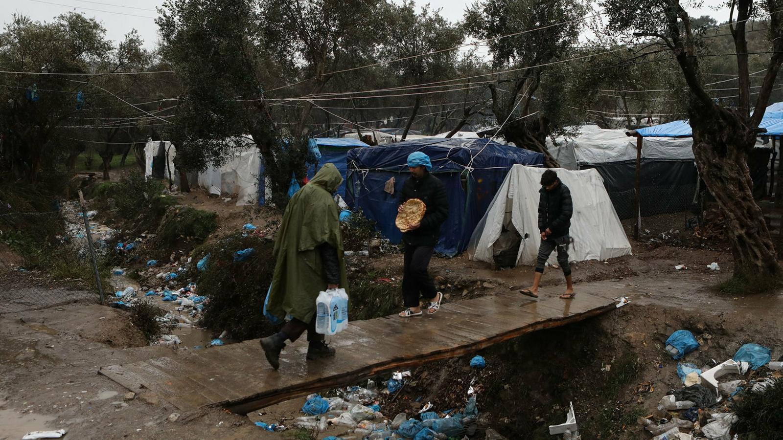 Refugiats caminant enmig de la pluja en un dels campaments a la rodalia del centre de detenció de Mória, a l'illa grega de Lesbos, aquest dijous.