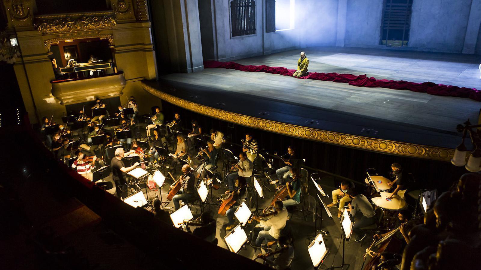 L'orquestra del Liceu en un assaig de Don Giovanni.  A la dreta, el director Josep Pons.