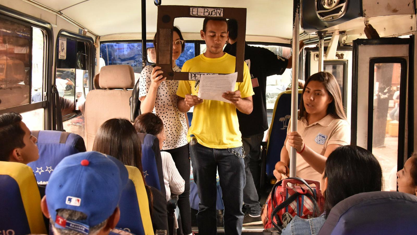L'Abraham llegint  les notícies  en un autobús mentre  la María Auxiliadora aguanta el marc de cartró.