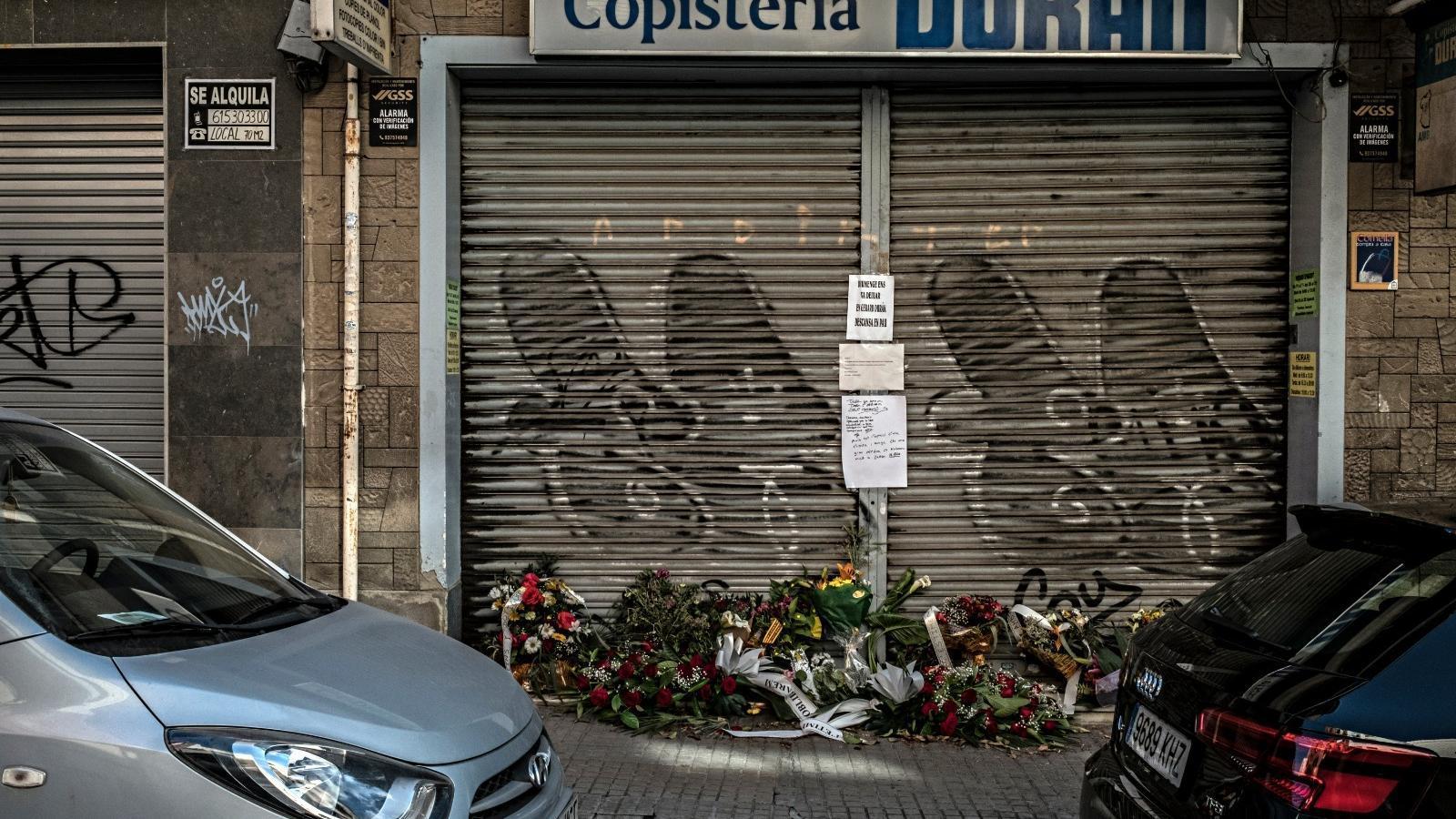 La porta de la copisteria Duran, de Cornellà, plena de flors i missatges de record, del veïns i amics del Gerard, per la seva mort, víctima de la pandèmia de covid-19