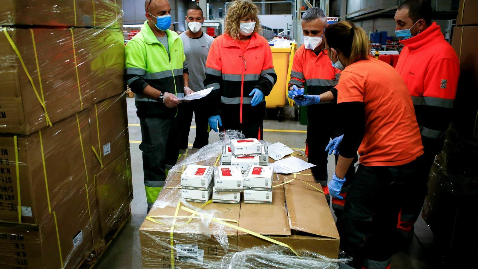 Treballadors de l'empresa Logaritme Servei Logistics IAE revisant el material sanitari a punt per ser distribuït a hospitals i residències de Catalunya / QUIQUE GARCÍA / EFE
