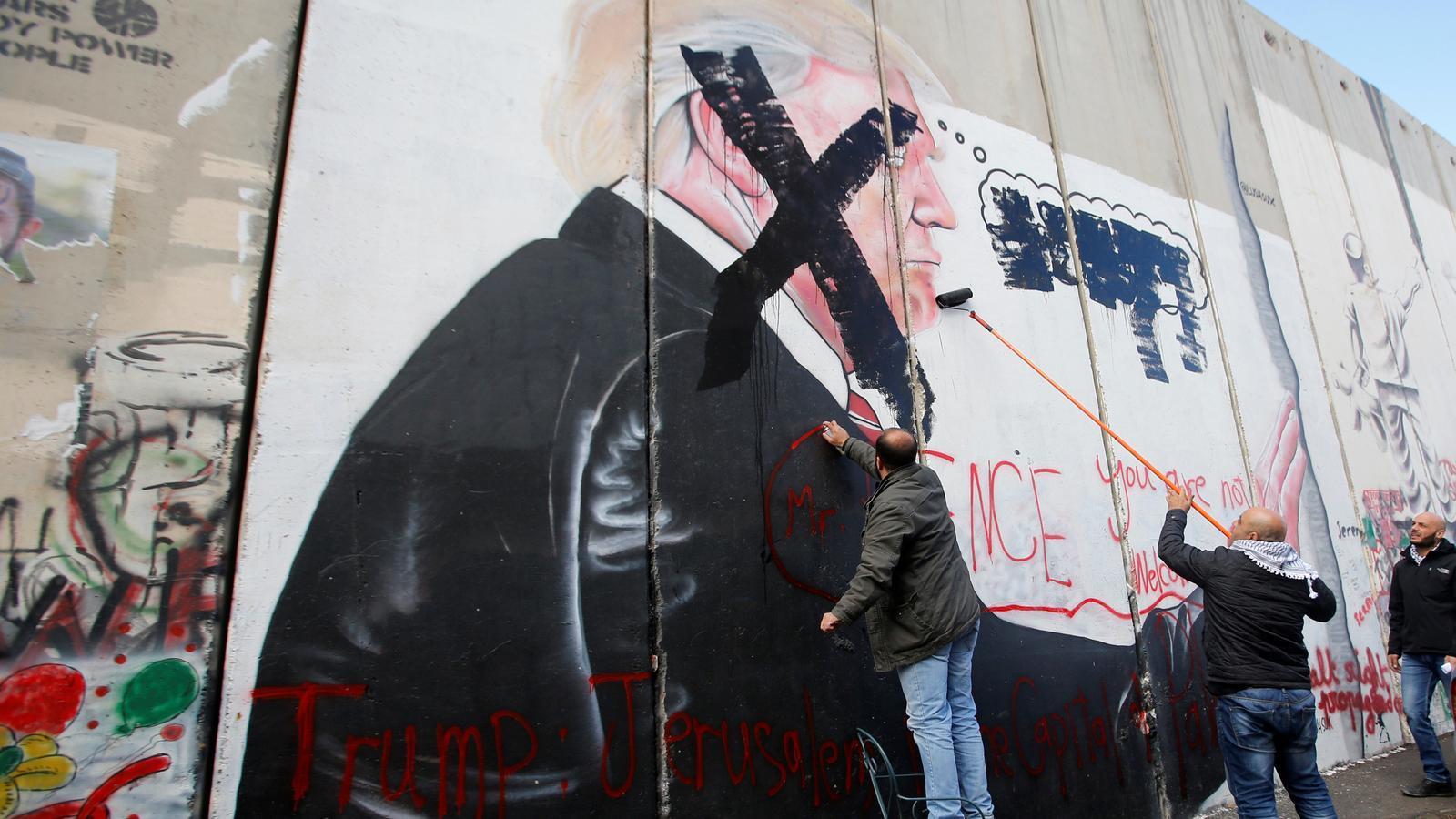 """Un home tatxa el rostre de Donald Trump al mur de Betlem mentre un altre escriu en lletres vermelles: """"Pence no ets benvingut"""""""