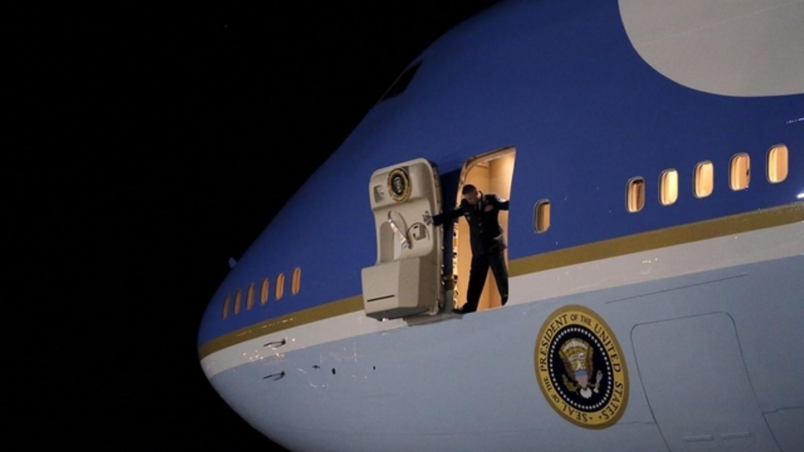 Un membre de la seguretat de la Casa Blanca obre la porta de l'Air Force One.
