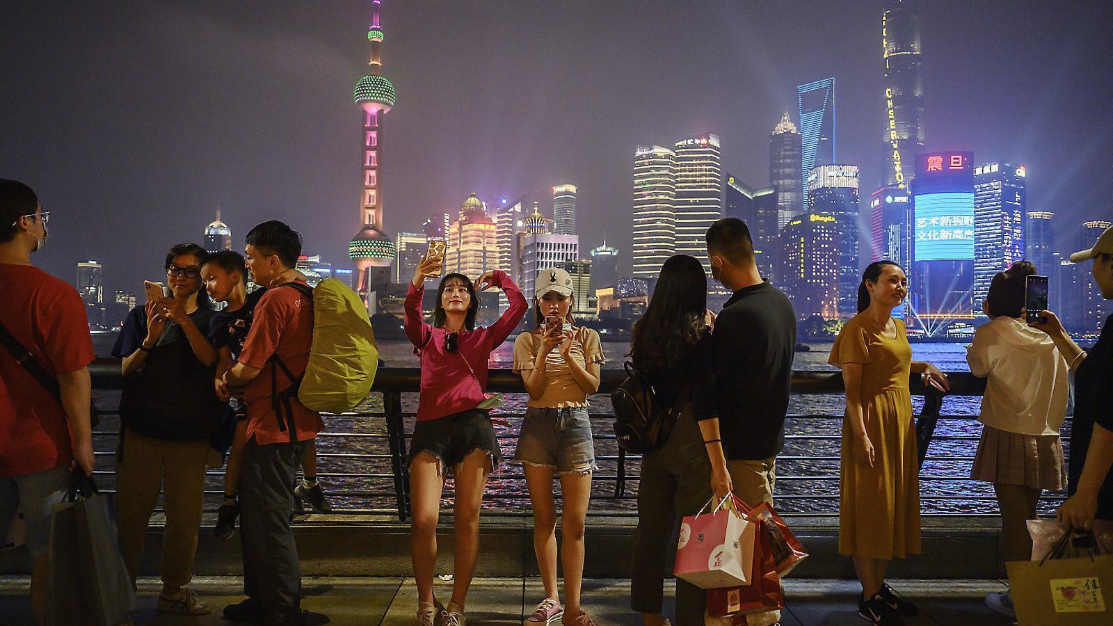Ambient aquest dissabte al vespre al passeig fluvial de Xangai. La Xina és un dels pocs països que probablement creixerà aquest 2020 i continuarà acostant-se als EUA.