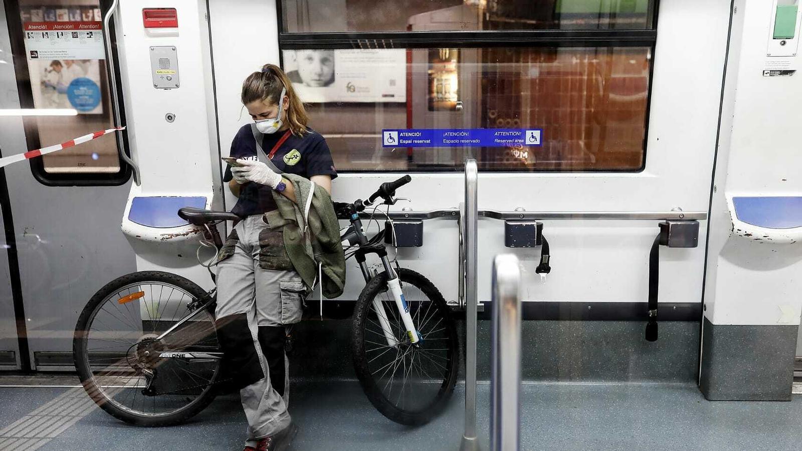 Una treballadora amb mascareta i guants dins d'un vagó de metro el primer dia feiner després que s'hagi aixecat el confinament total
