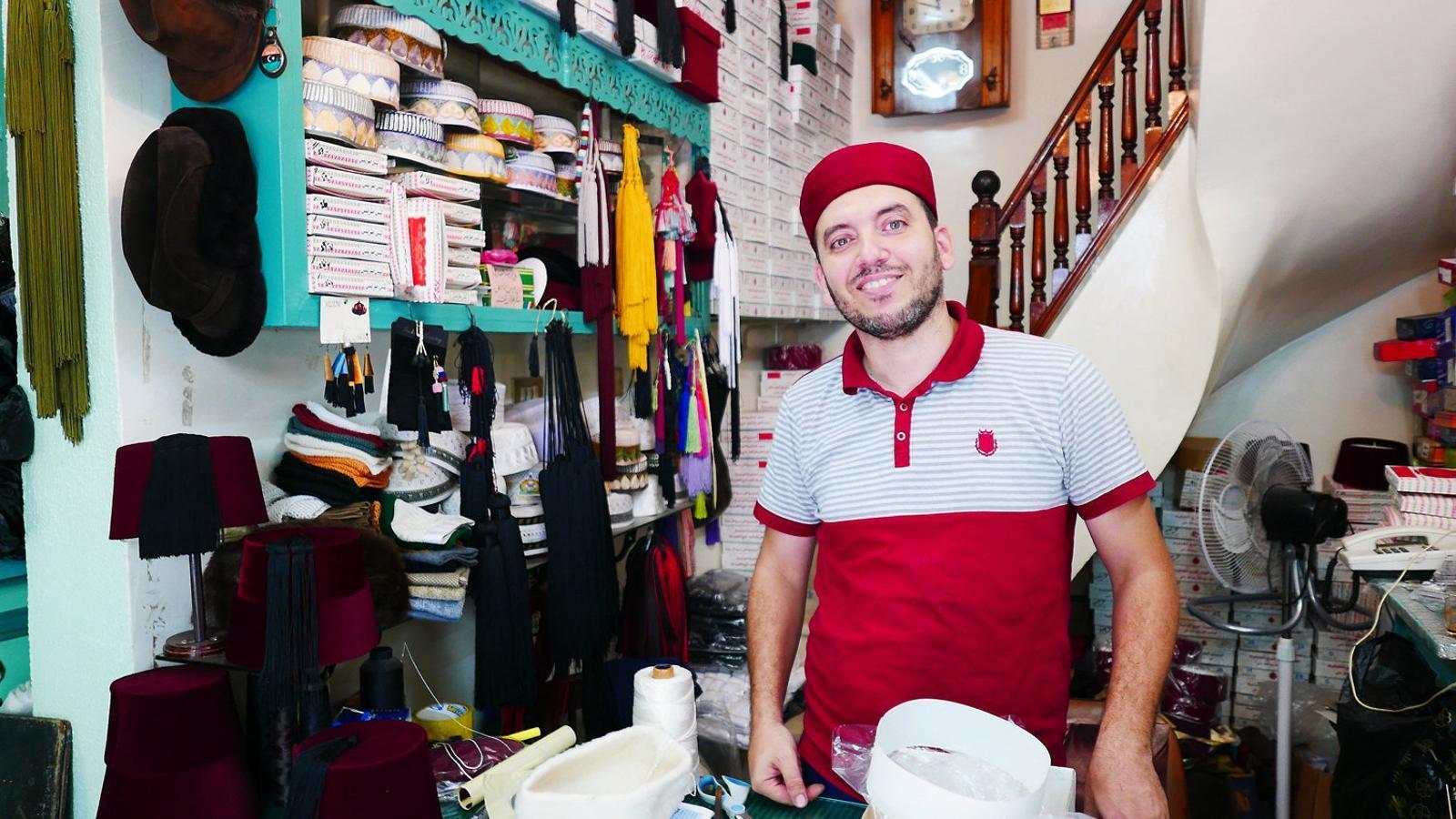 Mehdi Troudi és un jove artesà que ha heretat la botiga del seu pare i explica que exporta bona part de la seva producció de barrets.