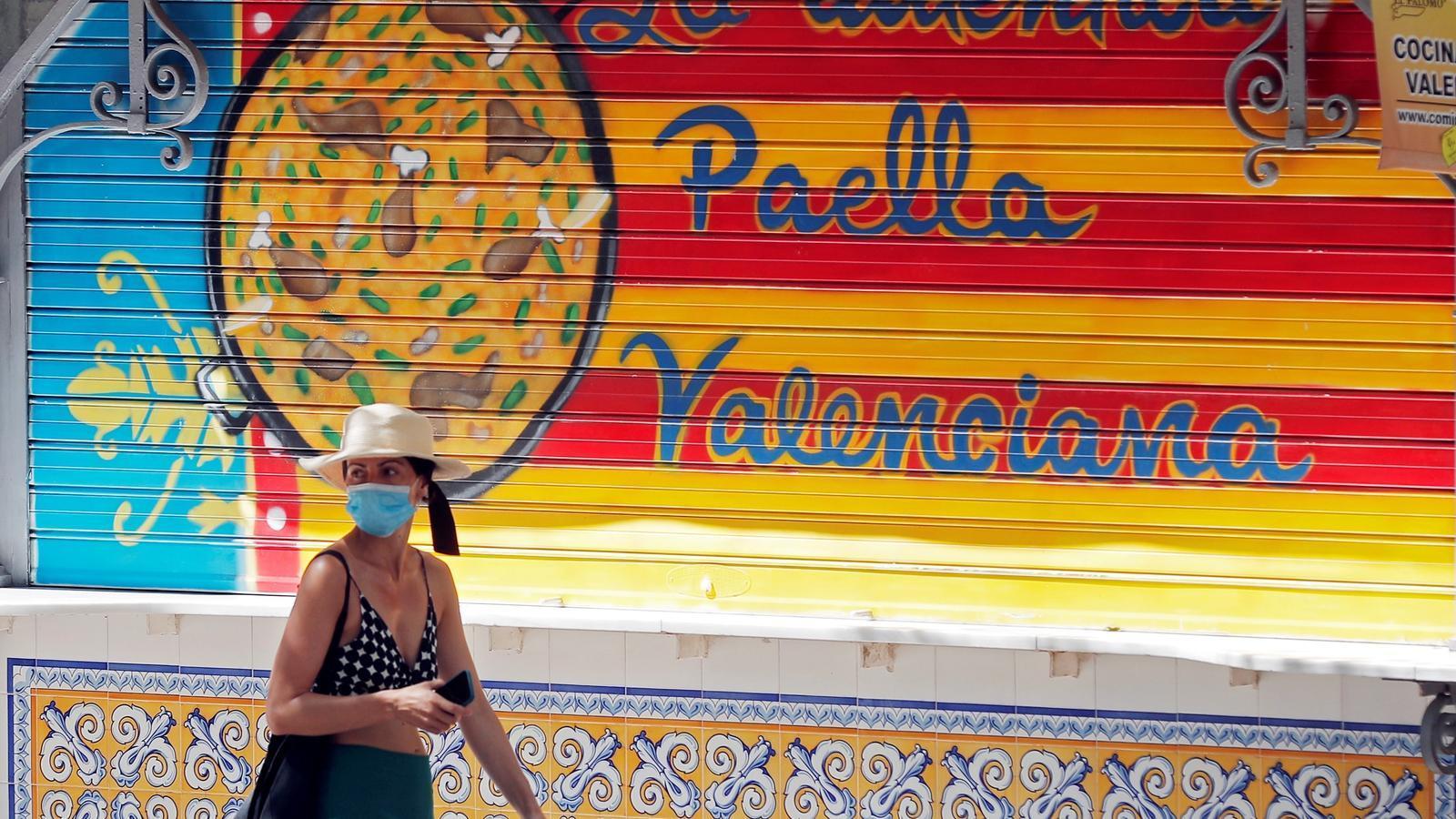 Una dona amb mascareta passeja davant d'un establiment especialitzat en la cuina de paelles