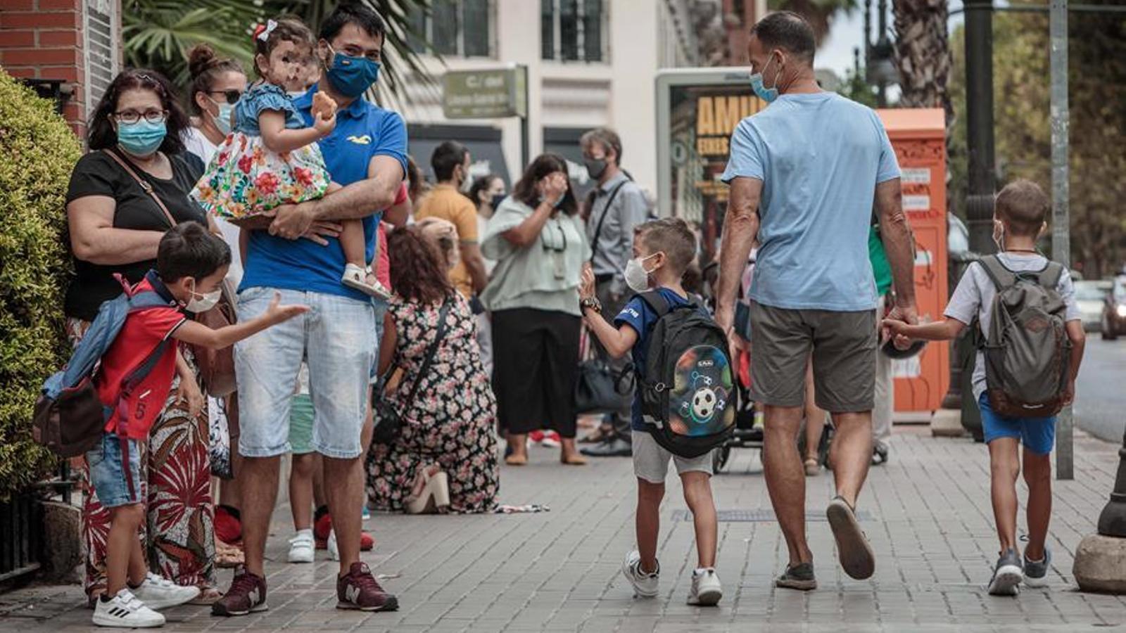"""Pares i mares fan cua enfront del col·legi Jesús i María de València a l'espera de poder deixar als seus fills durant el primer dia de classe per a 794.243 alumnes i 4.374 professors de 1.425 centres públics i 420 concertats de la Comunitat Valenciana en un """"excepcional"""" inici de curs, marcat per les mesures sanitàries que imposa la pandèmia de coronavirus i la incertesa del seu impacte i evolució. EFE/Biel Aliño"""