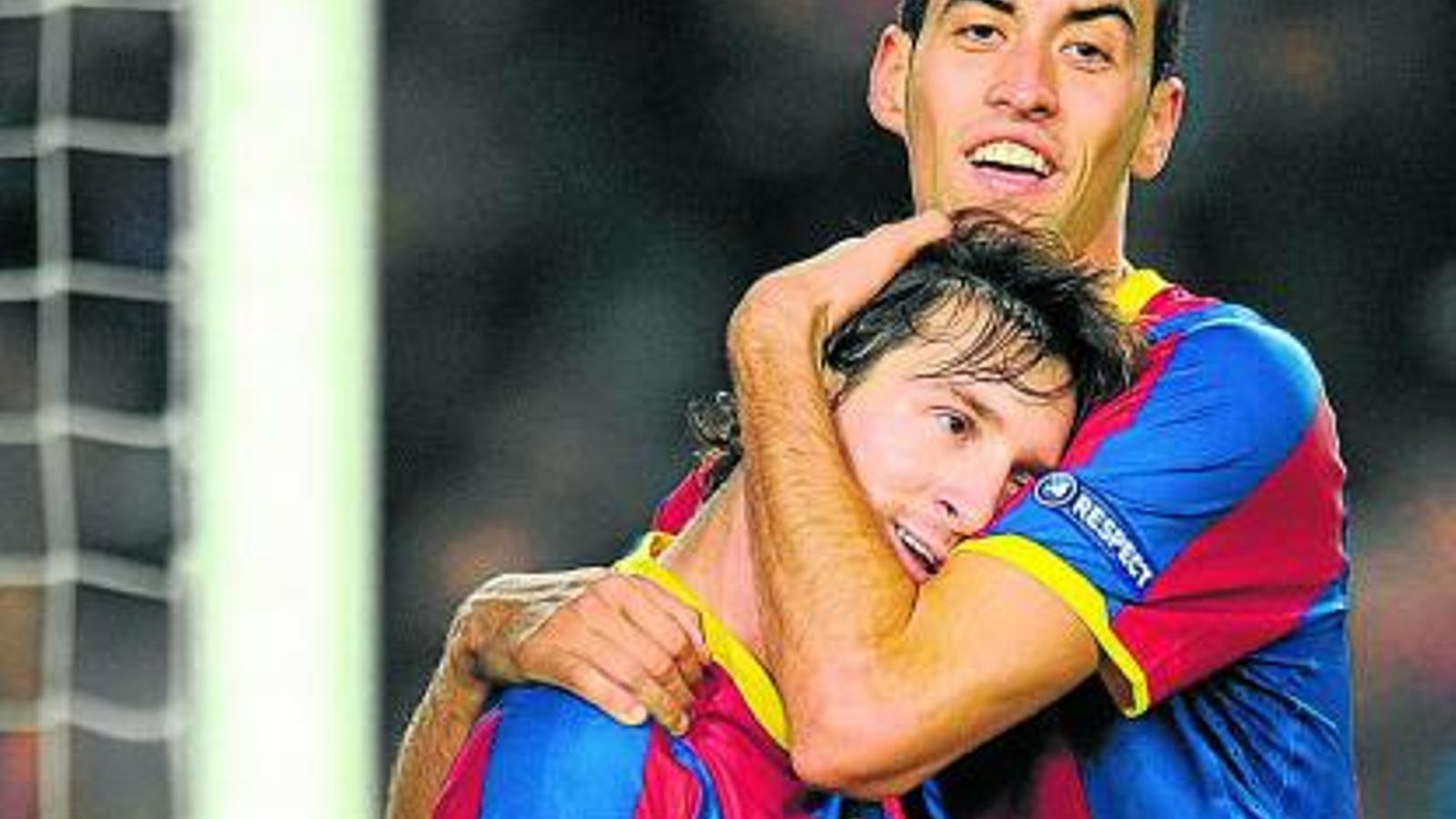 Sergio Busquets s'abraça a Leo Messi en un dels partits de la Lliga  de Campions d'aquesta temporada. / LLUÍS GENÉ / AFP