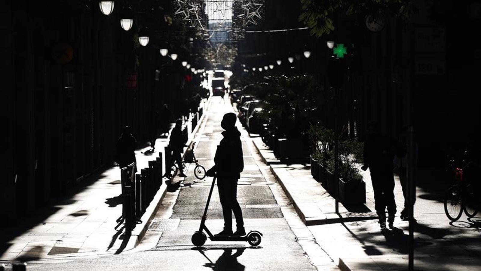 Una persona passeja en patinet pel centre de Barcelona