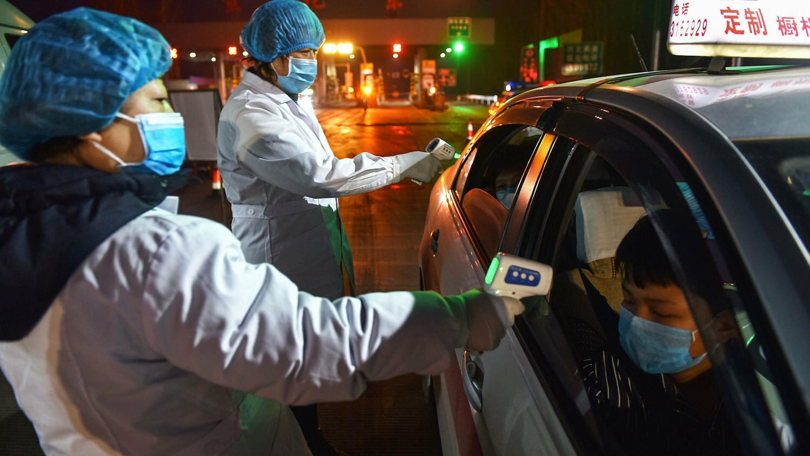 Operaris prenent la temperatura als ocupants d'un cotxe en una sortida d'una autopista a Zhangjiakou, a la província de Hubei, situada al nord de la Xina.
