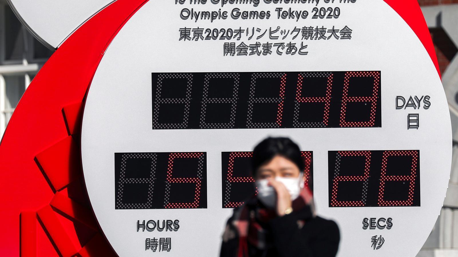 Una dona amb mascareta davant del rellotge que marca el compte enrere dels Jocs Olímpics Tòquio 2020, al Japó