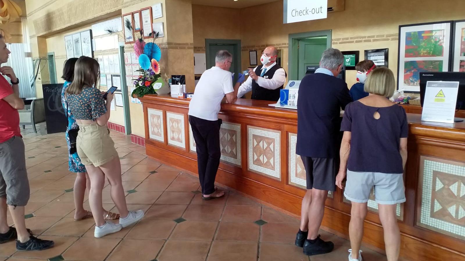 Un empleat, amb mascareta de protecció,  parla amb alguns clients., poc desprès de decretar-se el confinament