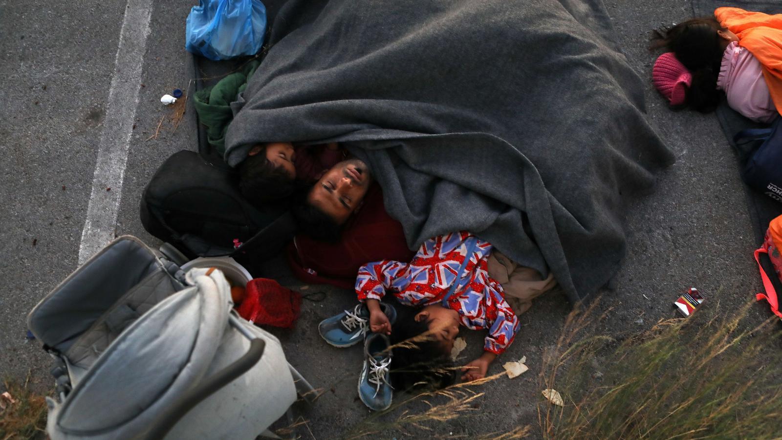 Una família dorm en una carretera propera al camp de refugiats després d'haver fugit de les falmes.