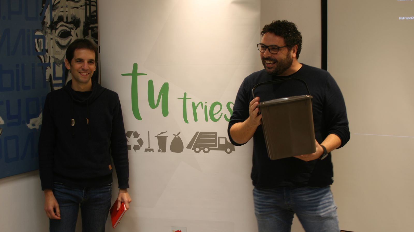 El tècnic de medi ambient Antoni Pasqual i el regidor Sebastià Llodrà amb el poal que es fa servir per a matèria orgànica.