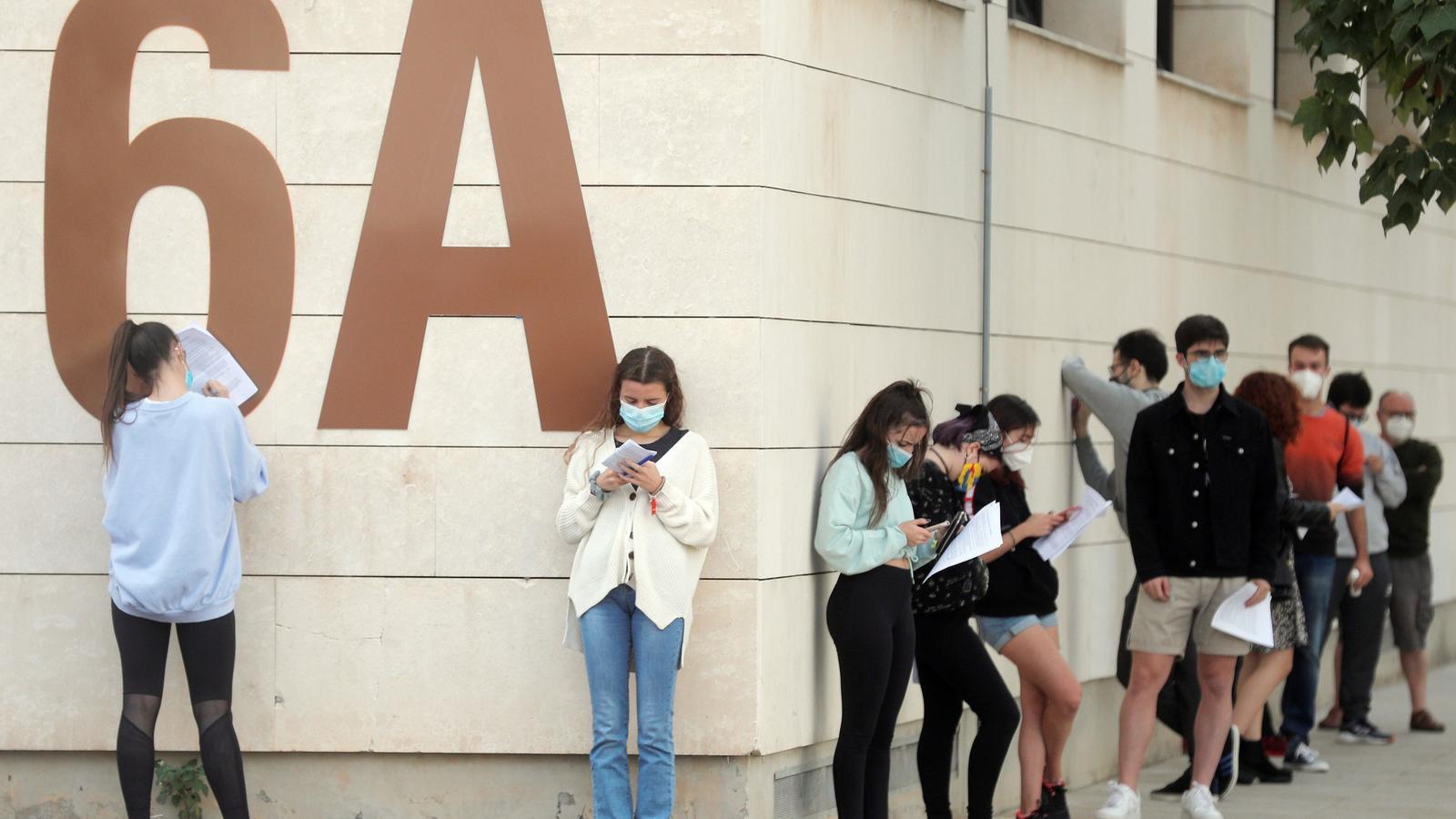 Estudiants de la Universitat Politècnica de València (UPV) fan cua en l'exterior de les instal·lacions del pavelló de bàsquet on es realitzen proves PCR