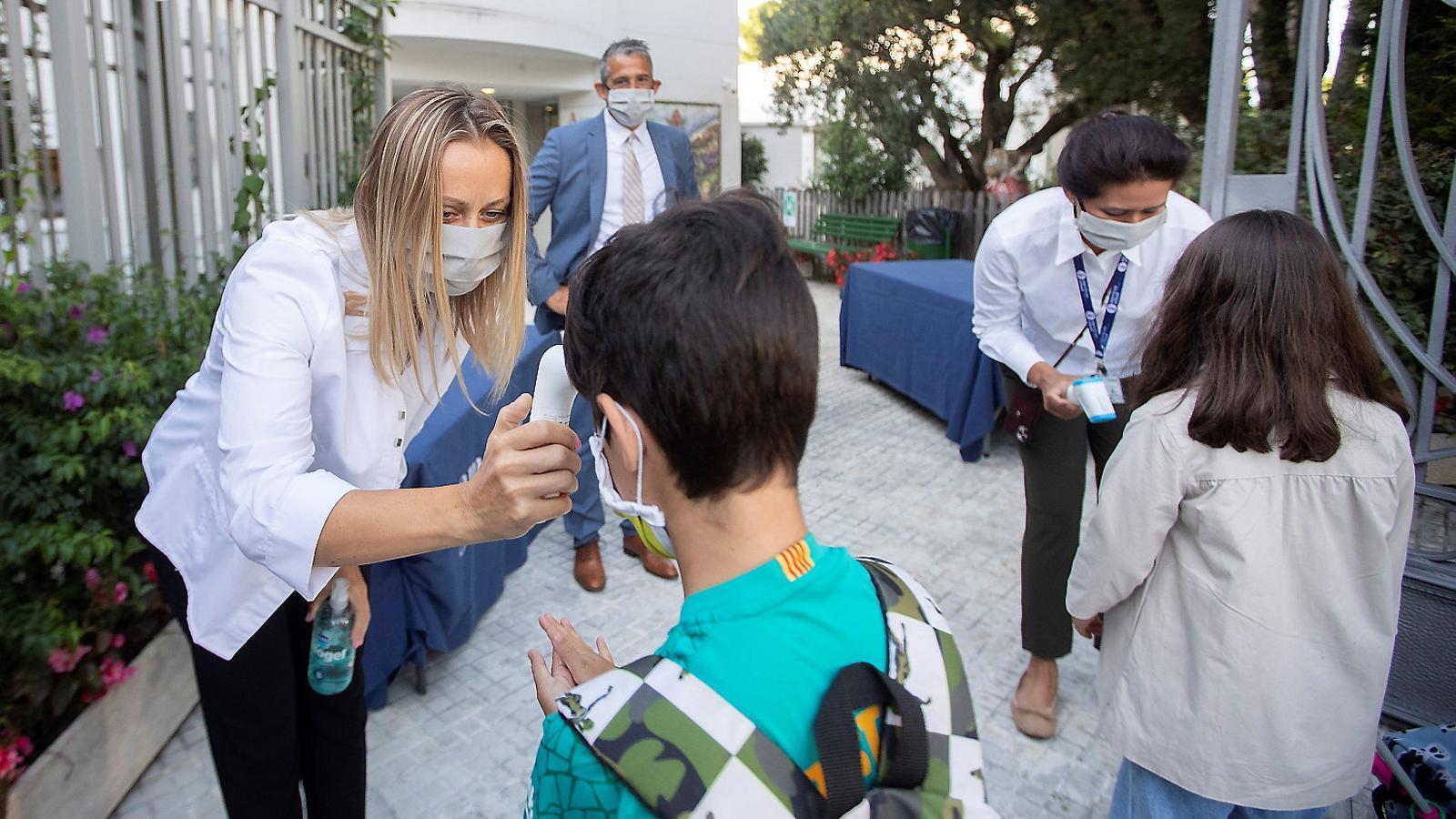 Una mestra de l'American School Barcelona, el primer centre que ha iniciat el curs a l'Estat, prenent la temperatura a un nen.