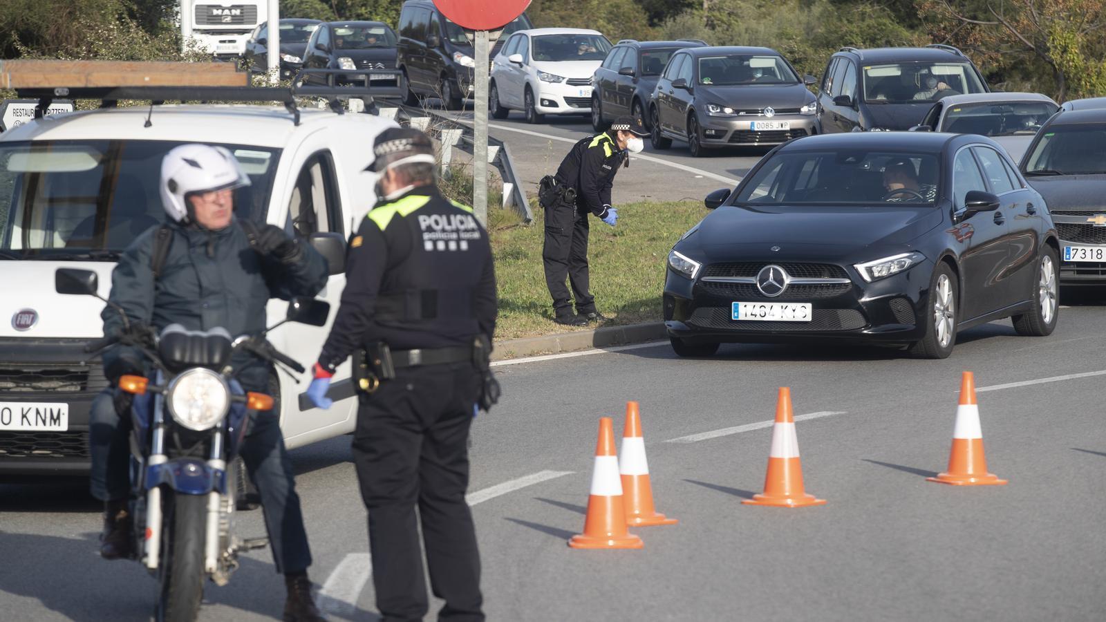 Agents de policia local fent un control als vehicles per comprovar si compleixen el confinament
