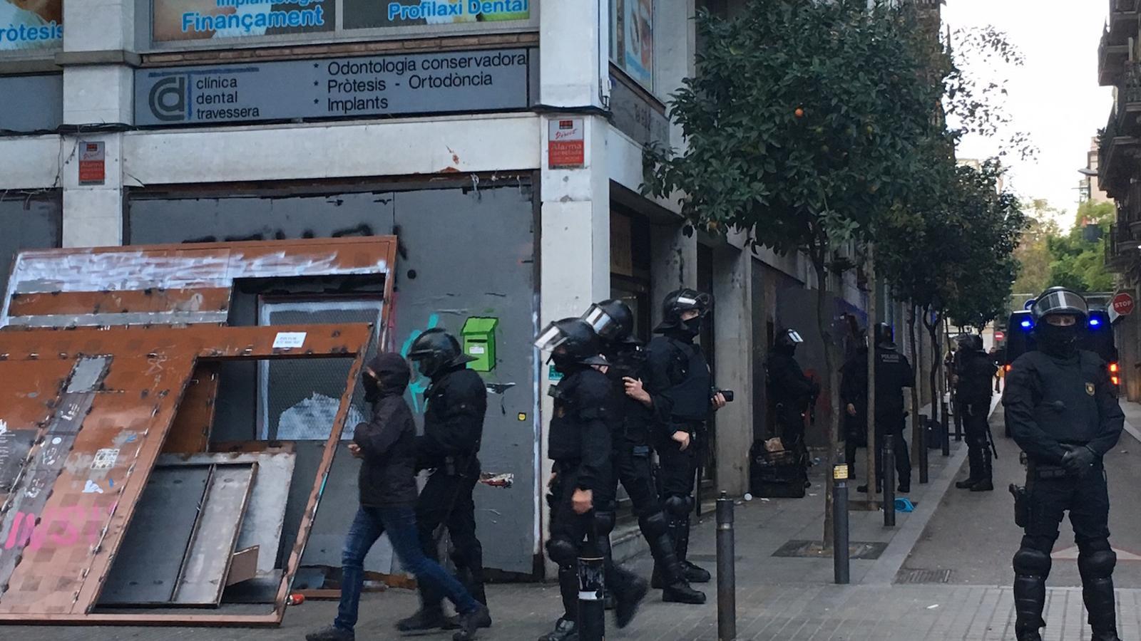 Agents antiavalots dels Mossos d'Esquadra s'enduen un dels activistes que ocupaven el Banc Expropiat de Gràcia, encaputxat i vestit de fosc, gairebé del mateix color que els policies / ENRIC BORRÀS