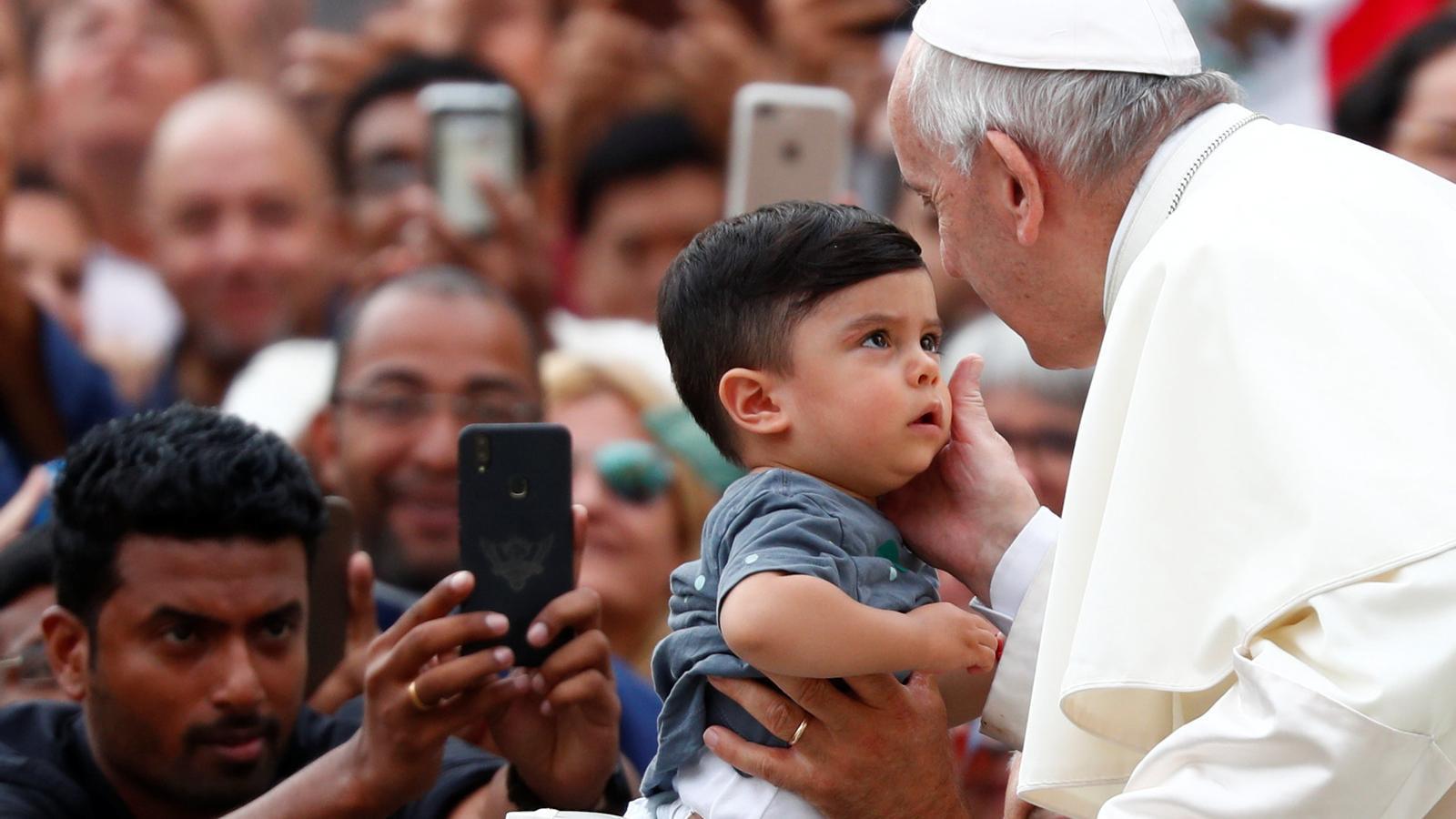 El papa Francesc acarona un infant durant la seva arribada a la Plaça Sant Pere del Vaticà.