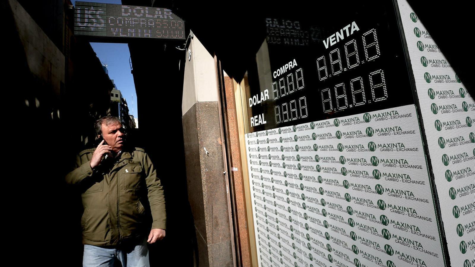 Un vianant observant els cartells que informen del canvi del peso enfront del dòlar després de dues jornades de fortes caigudes, ahir, a Buenos Aires.