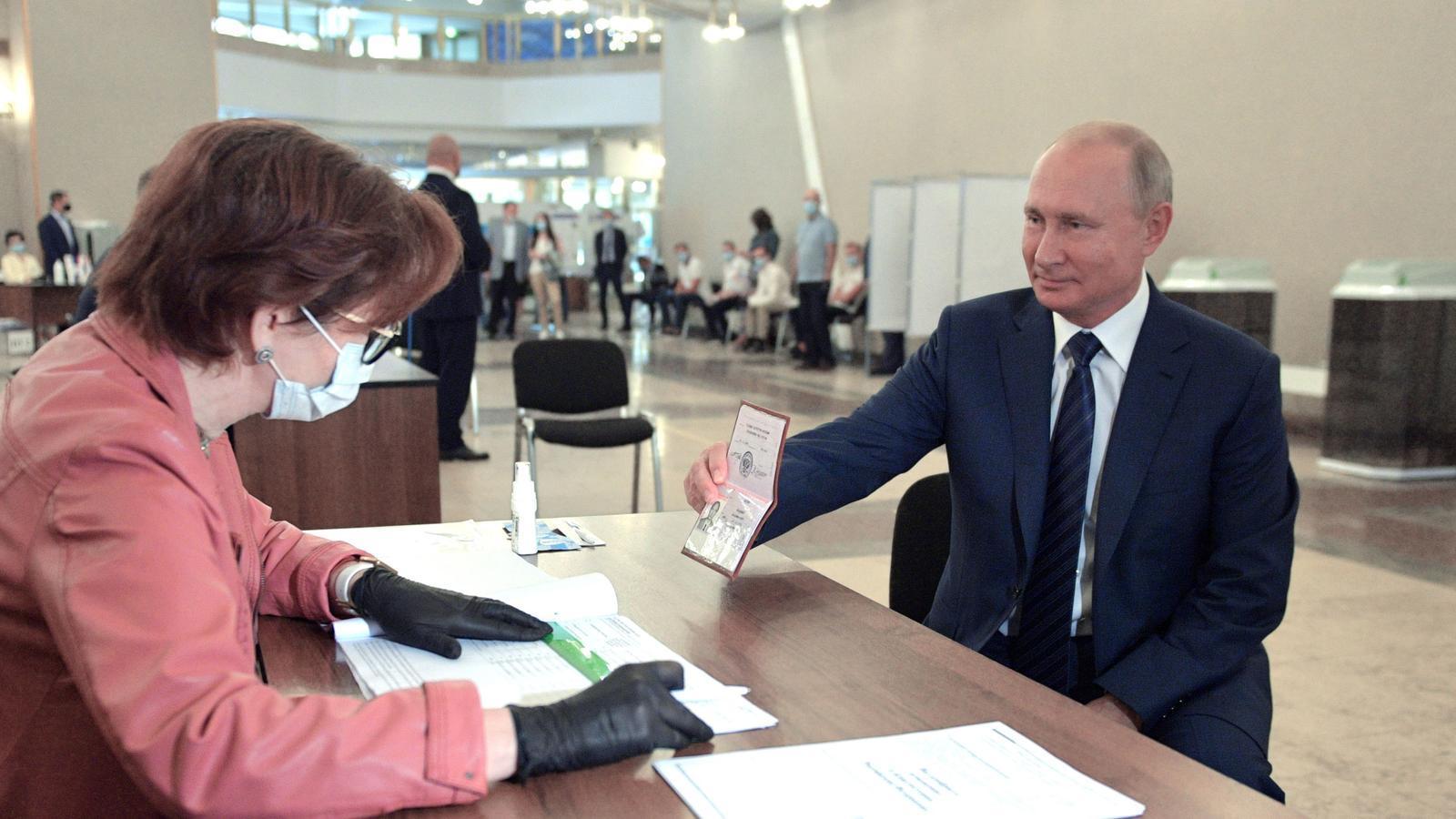 El president rus Vladimir Putin mostra el seu passaport en un col·legi electoral de Moscou, Rússia