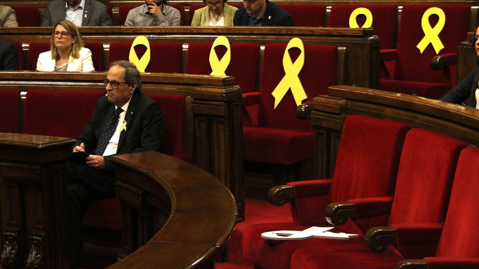 Un llaç groc a la bancada del Govern tombat amb Quim Torra, de fons, i amb altres llaços de fons al ple d'aquest divendres