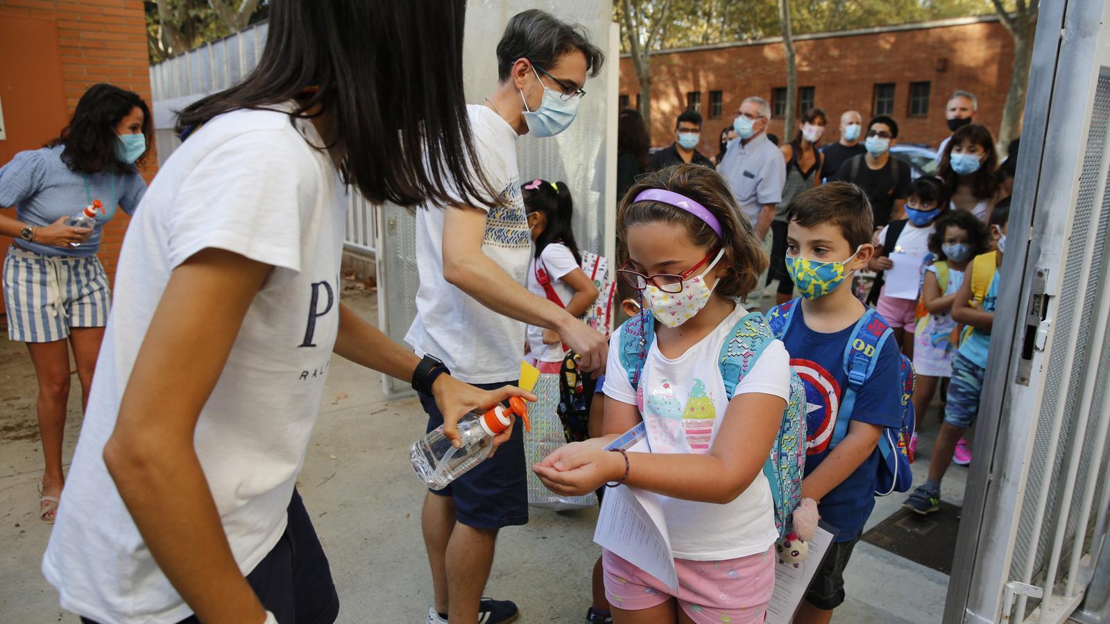 Professors rebent els alumnes a la porta de l'escola per fer les entrades esglaonades i garantir la higiene de mans.
