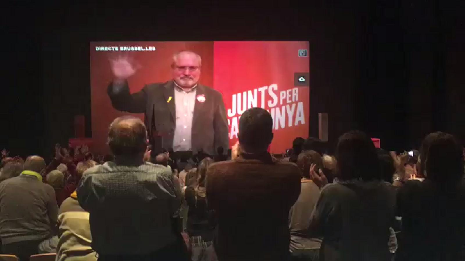 Lluís Puig, que també és de Terrassa, s'emociona en connectar en directe des de Brussel·les i veure el teatre ple. Hi ha la seva família a la primera fila