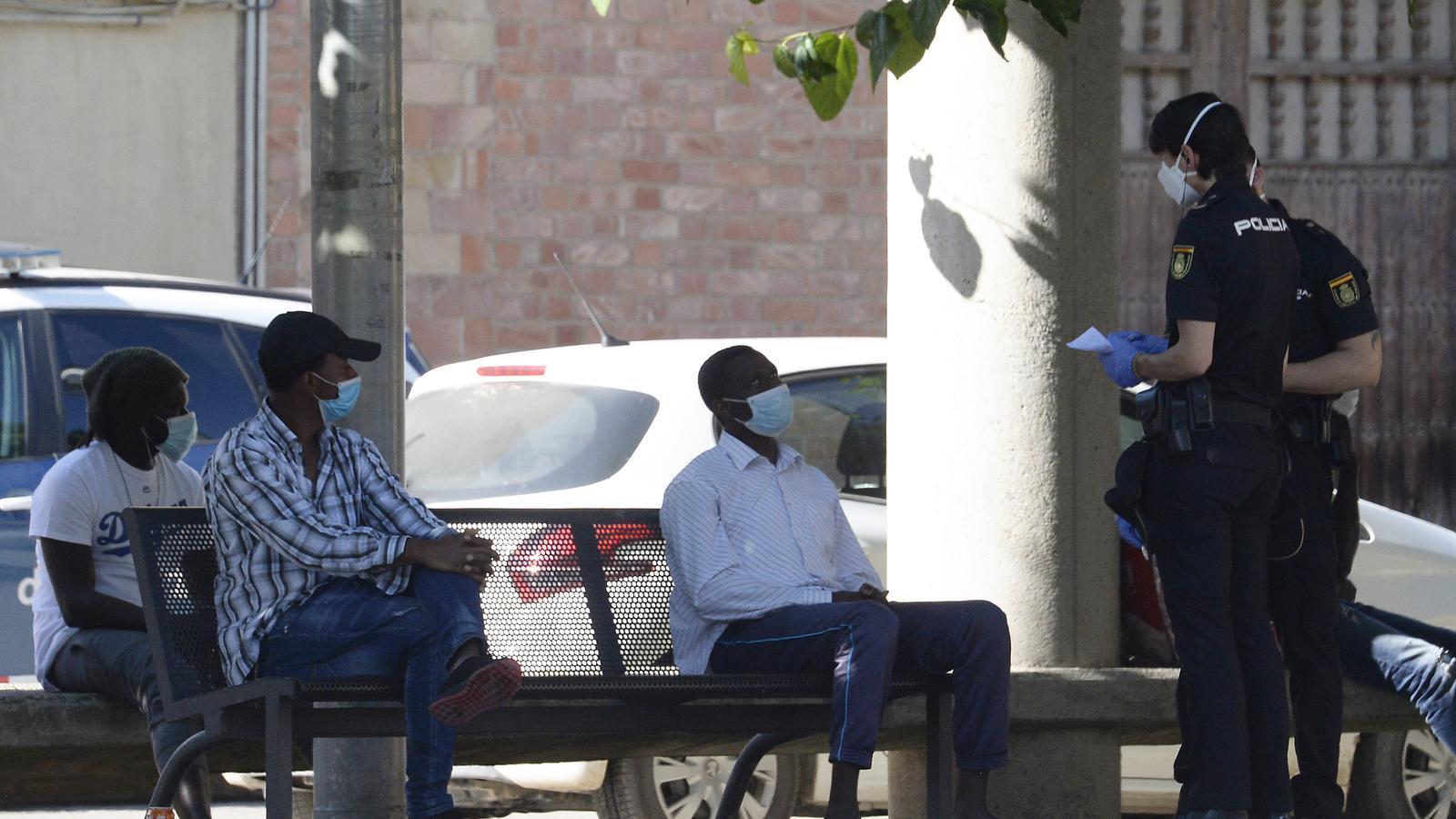 Agents de la policia demanen la documentació als immigrants que hi ha a la plaça del Toll d'Alcarràs