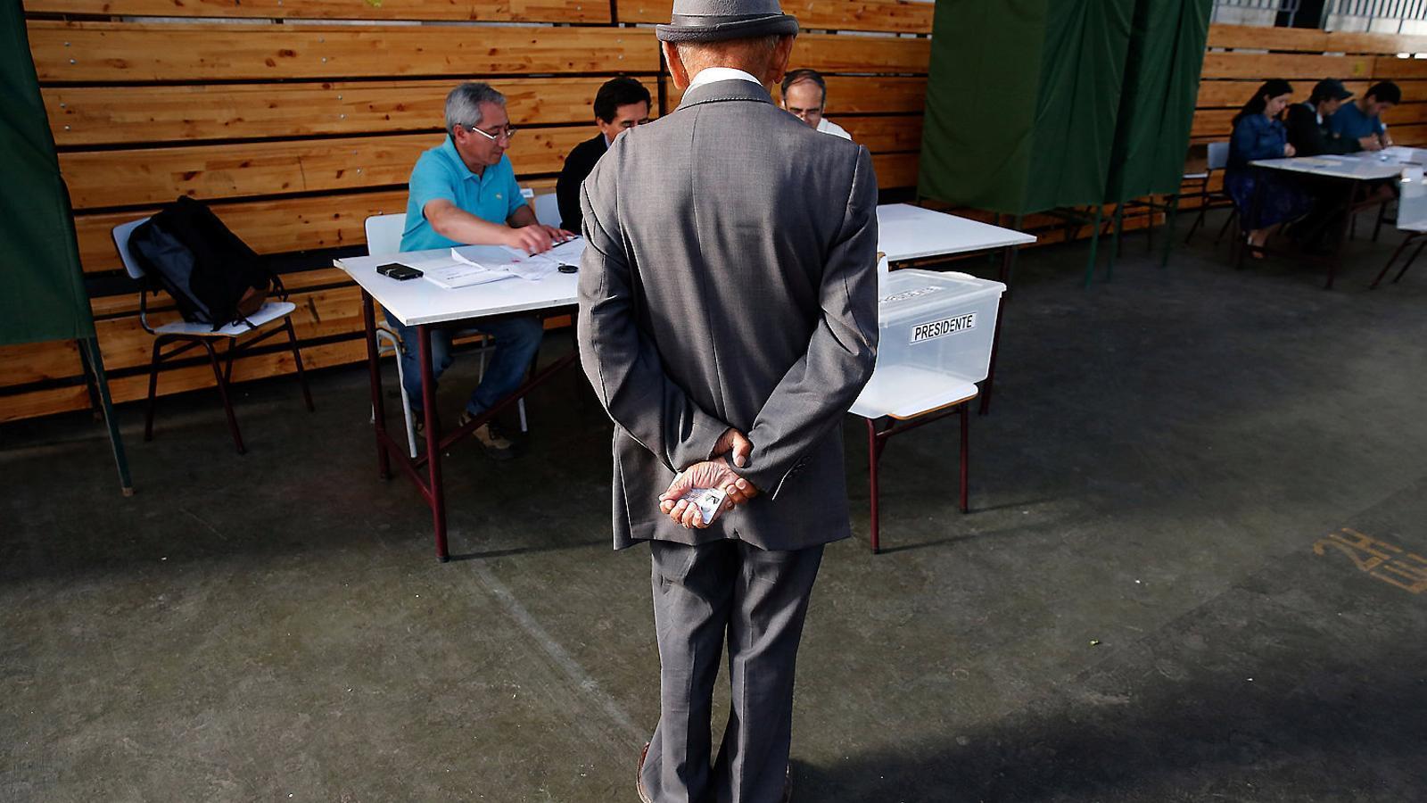 Un home esperant el torn per votar en un dels centres de votació situats a Santiago de Xile, la capital del país.