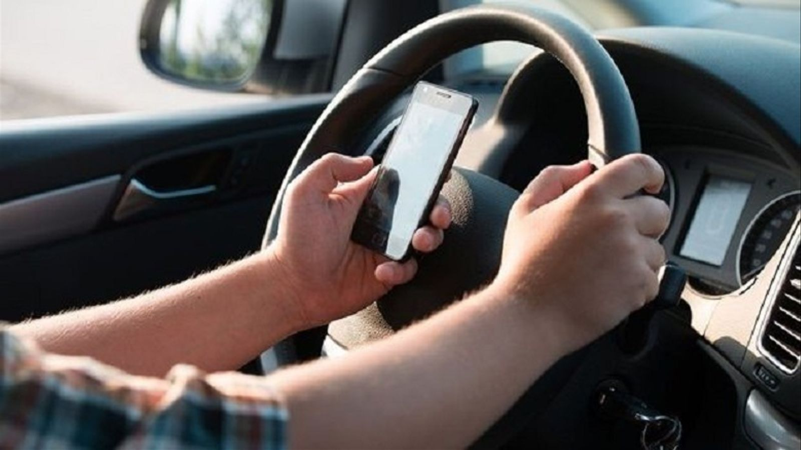 Un conductor amb el seu mòbil.