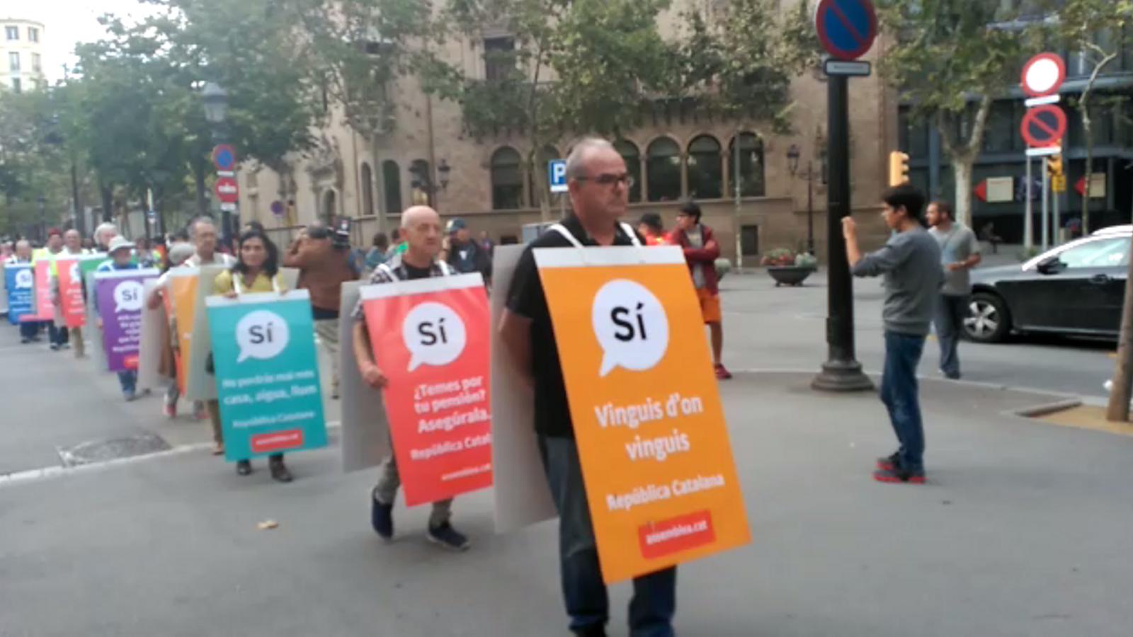 Membres de l'ANC baixant la Rambla Catalunya vestits amb els cartells