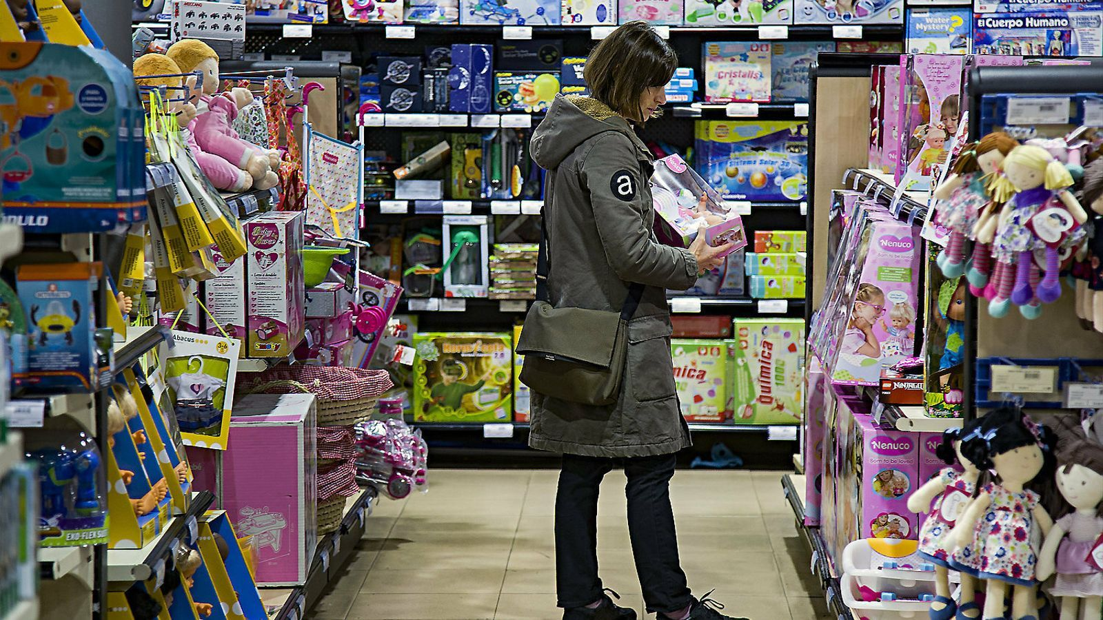Una dona busca un regal per a un infant en una botiga de joguines.
