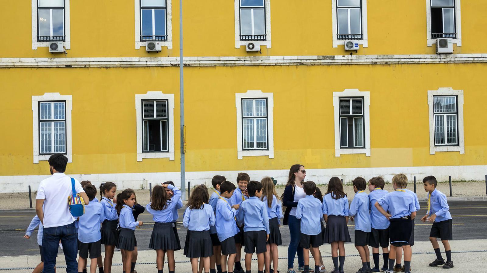 Alumnes d'un centre públic fent cua en un carrer del centre de Lisboa en una sortida escolar. / JEFF GREENBERG / GETTY
