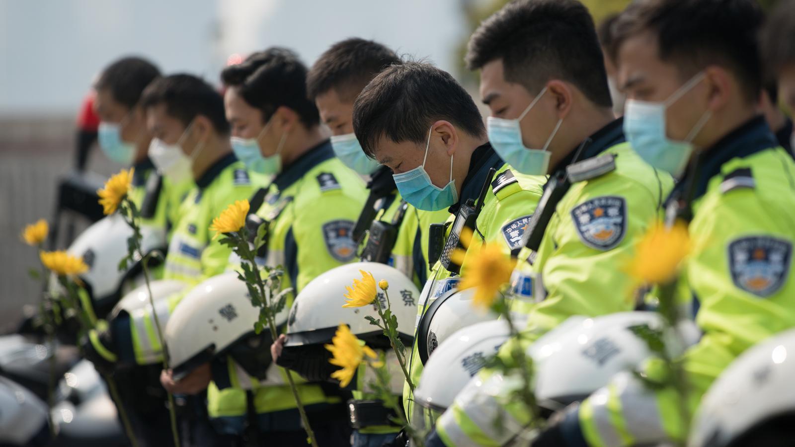 Un grup de policies guarda tres minuts de silenci per  les víctimes mortals del coronavirus a la Torre Memorial dels Herois del Poble a Xangai