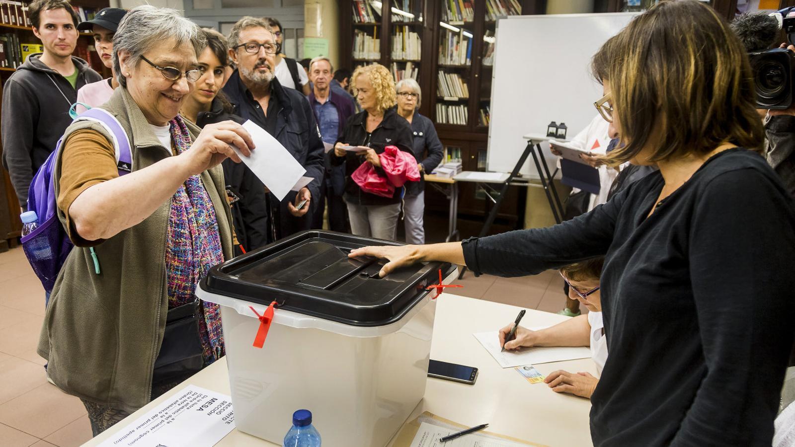 Una dona dipositant  la papereta en un col·legi electoral de Barcelona durant el referèndum de l'1 d'octubre del 2017.