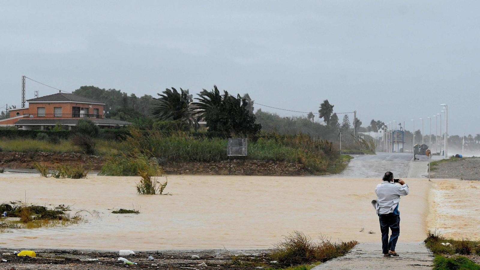 Un home fent una fotografia d'un carrer inundat a Benicarló, a la província de Castelló.