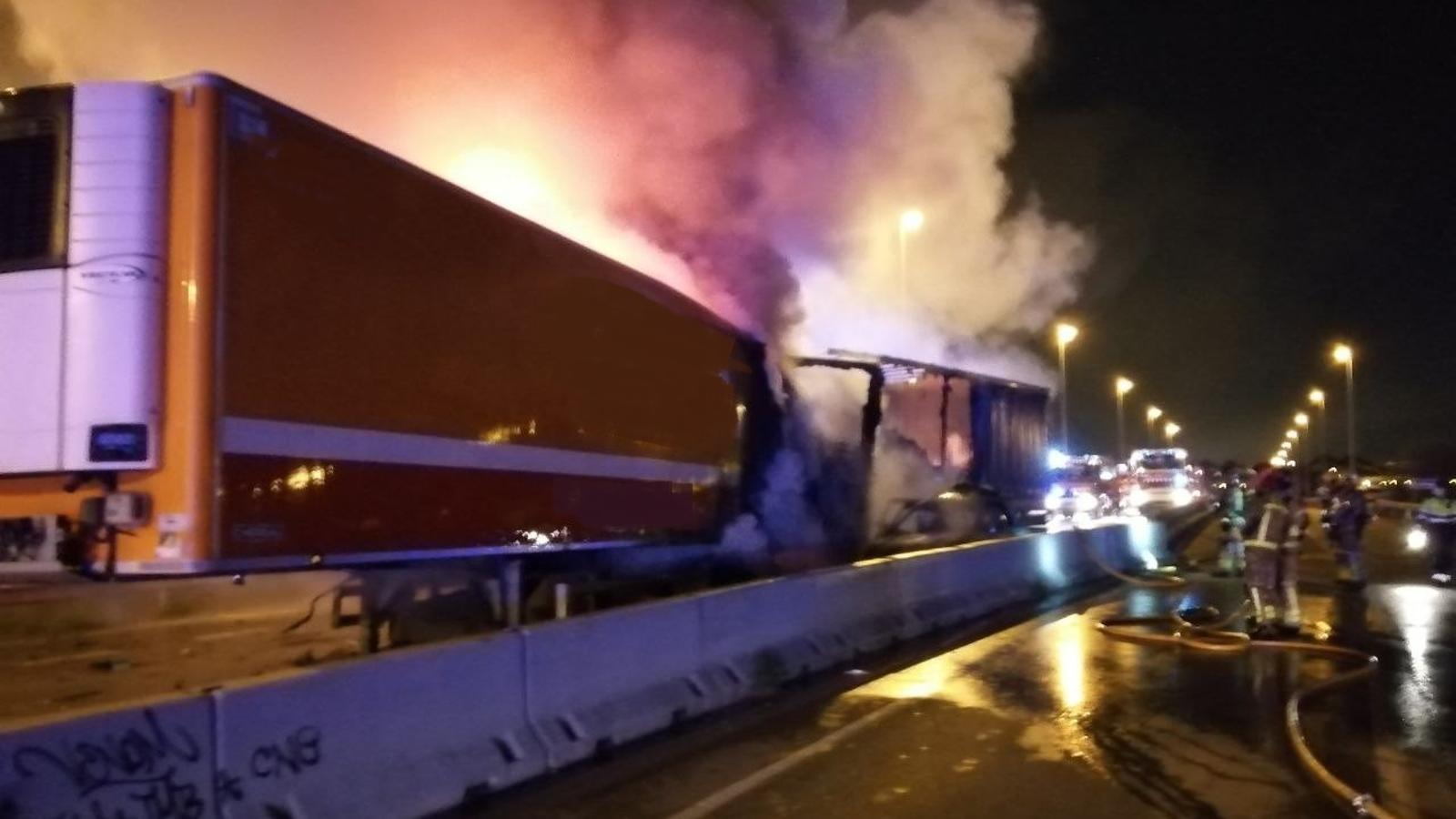 Els bombers apagant l'incendi que va afectar un dels camions i el cotxe