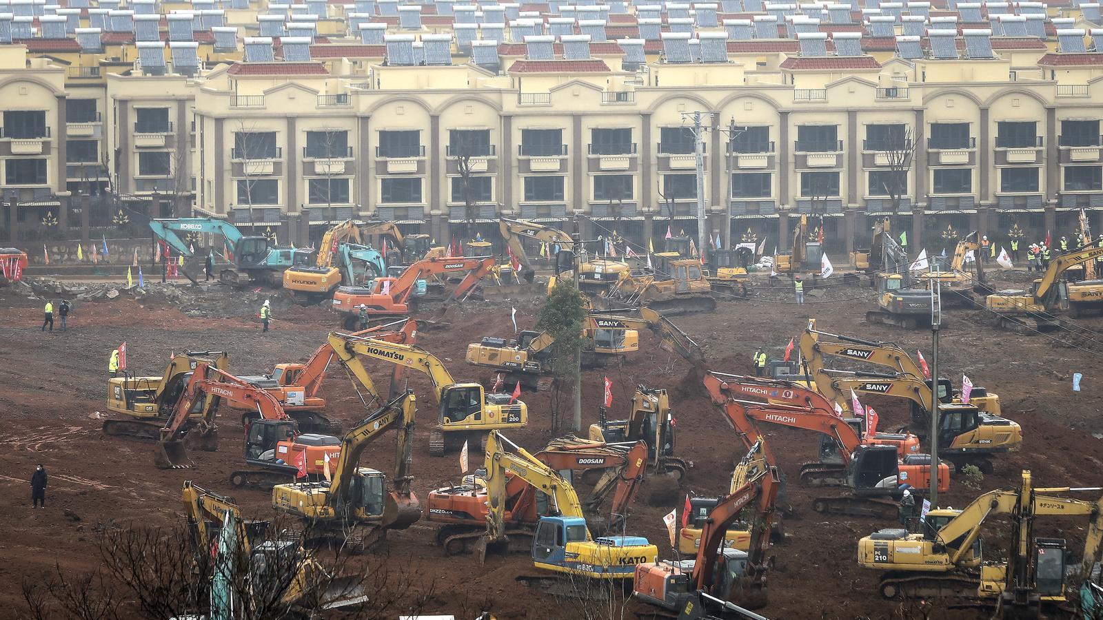 Treballadors conduint excavadores al lloc de construcció d'un hospital de camp a Wuhan. Els constructors tenen previst acabar l'hospital, de 1.000 llits, el 3 de febrer