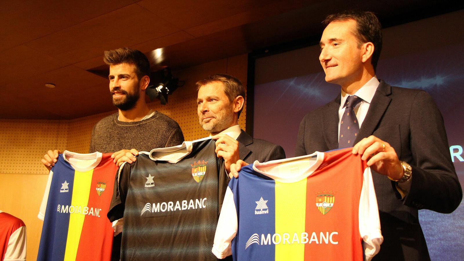Gerard Piqué, fundador i president de Kosmos; Lluís Alsina, director general de MoraBanc, i Ferran Vilaseca, Kosmos Head of Division, amb la samarreta de l'FC Andorra. / C. G. (ANA)
