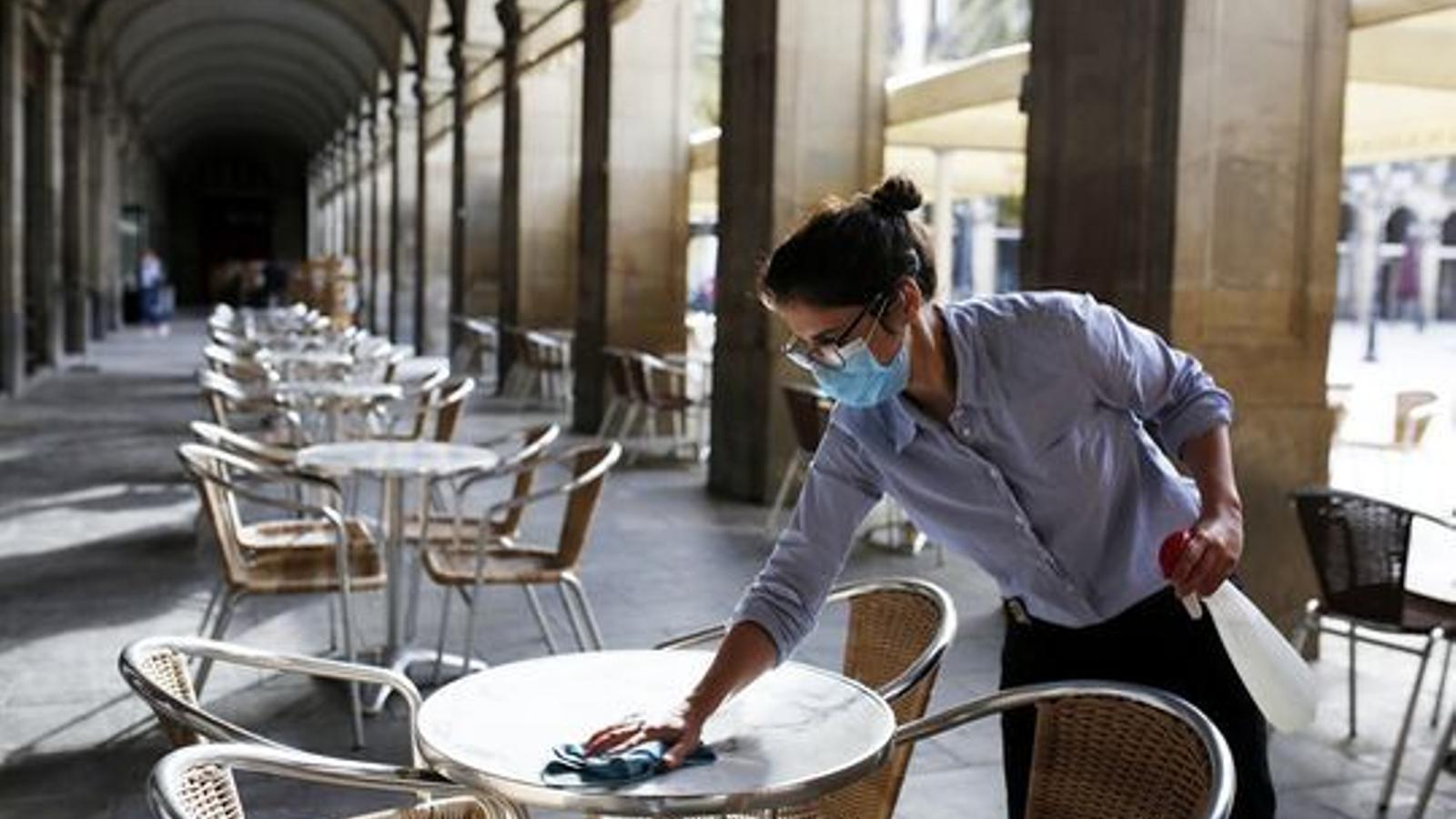 Una treballadora neteja una de les taules d'un restaurant de Barcelona