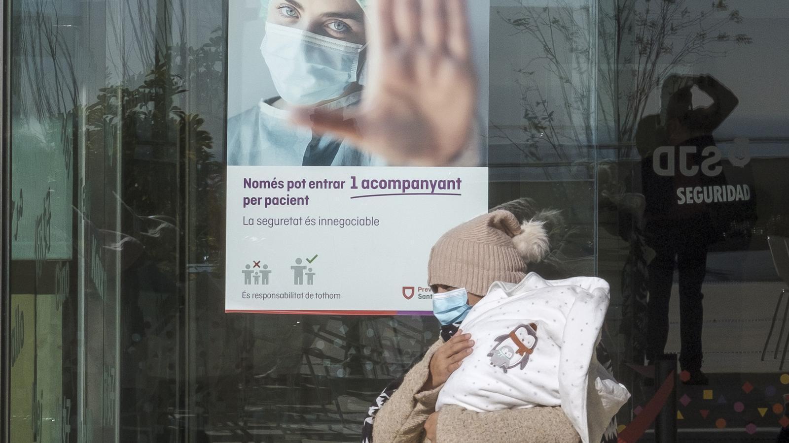 Una dona surt amb el seu nadó aquest dissabte del servei d'urgències pediàtriques de l'Hospital Sant Joan de Déu de Barcelona