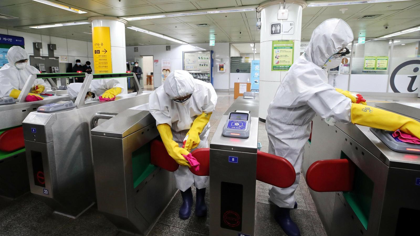 Treballadors netegen el mobiliari del metro a Seül, Corea del Sud.