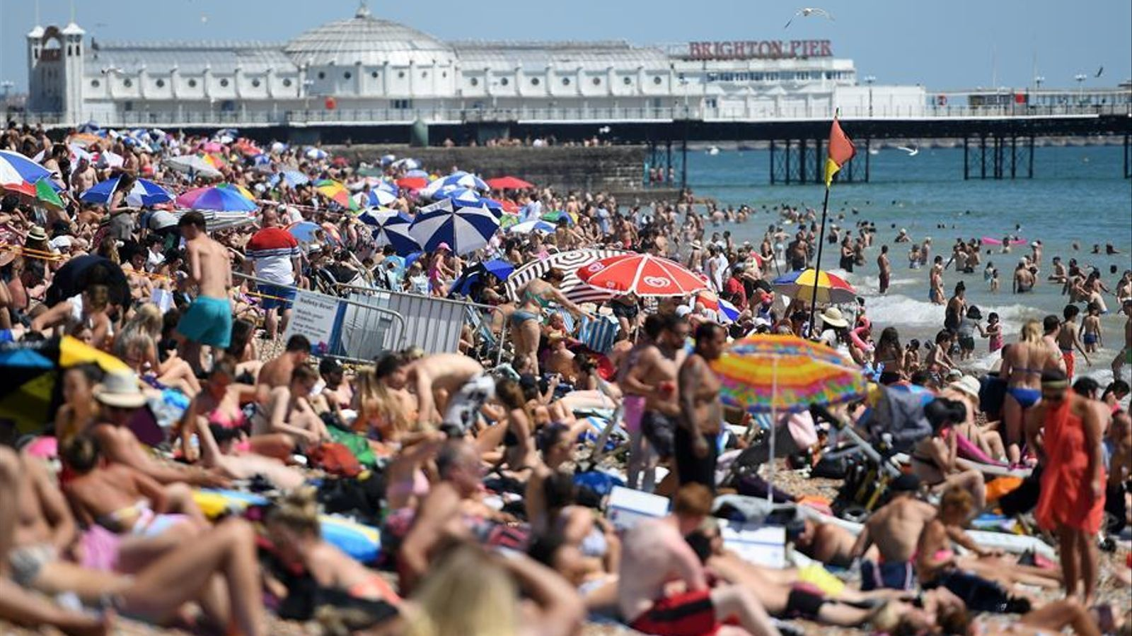 La platja de Brighton, al sud d'Anglaterra, plena de gom a gom de banyistes