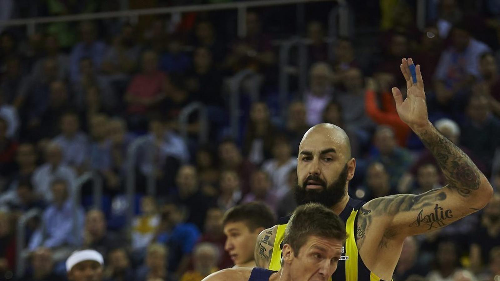 Justin Doellman, aler pivot del Barça Lassa, intentant superar Pero Antic, pivot del Fenerbahçe.