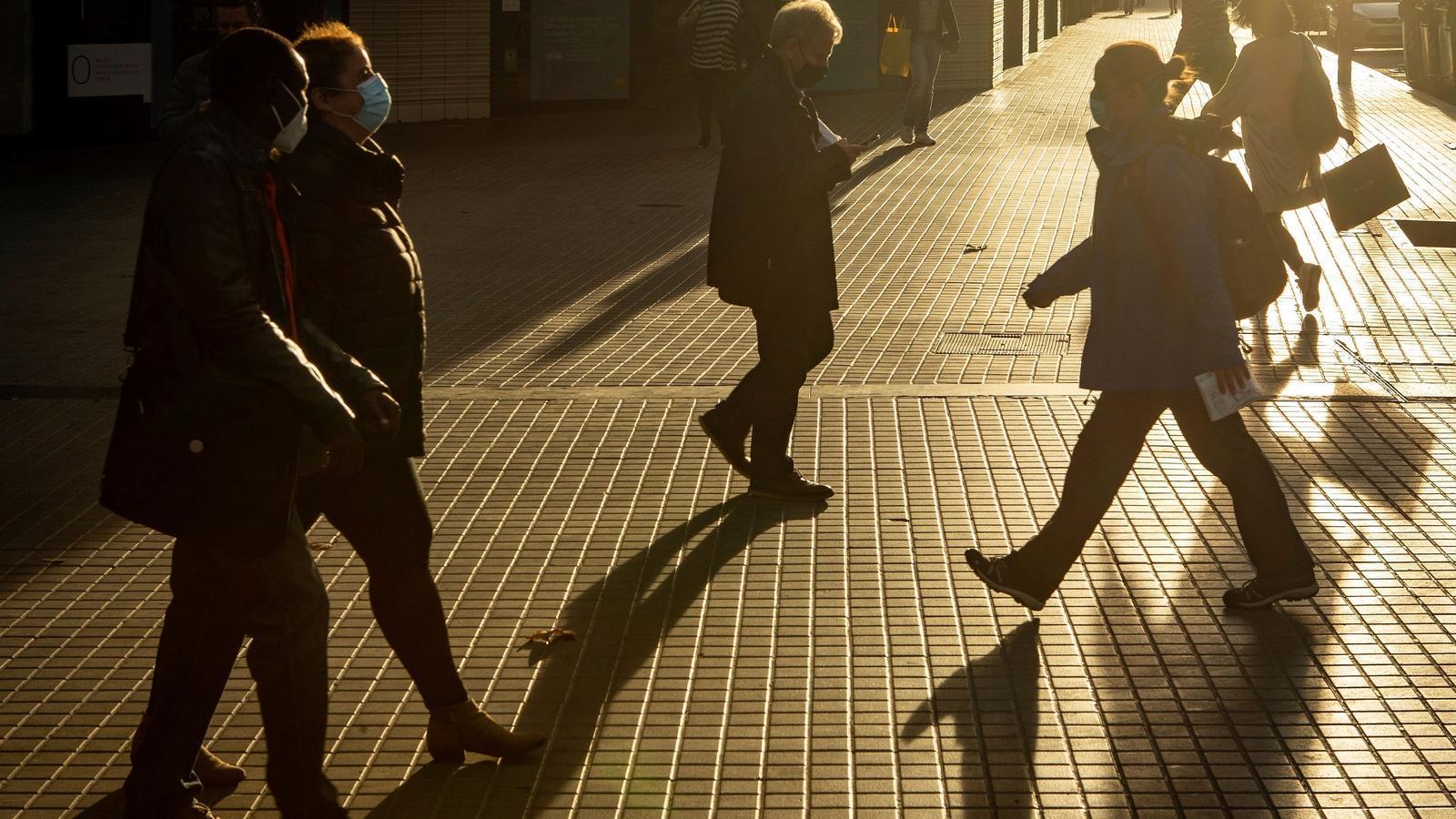 Diverses persones amb mascareta passejant pel carrer a Barcelona, aquest dilluns